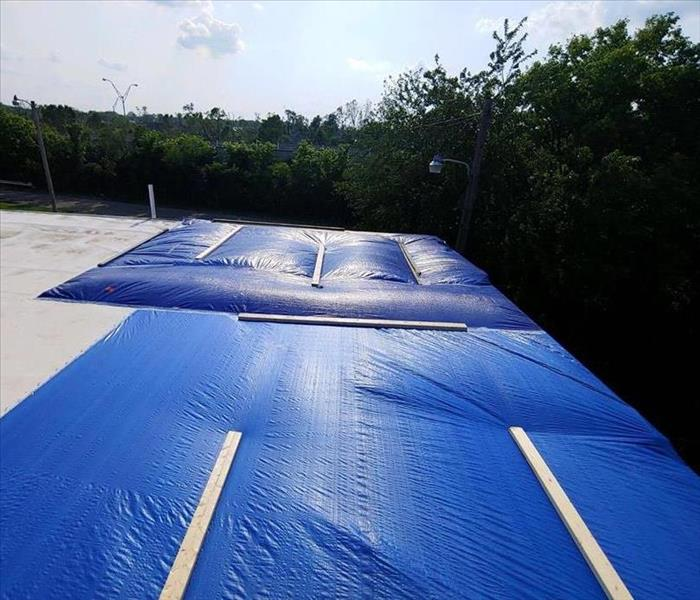 A restored roof after storm damage, covered in a tarp.
