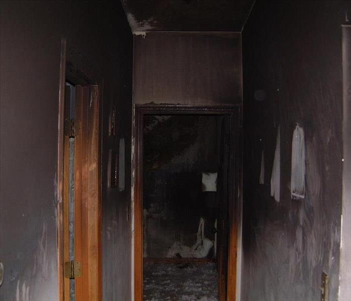 A hallway completed burnt, the walls black from smoke stains.