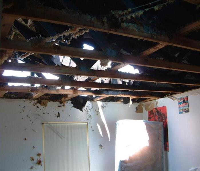 A ceiling exposing the sky due to fire damage that destroyed the structure of the home.