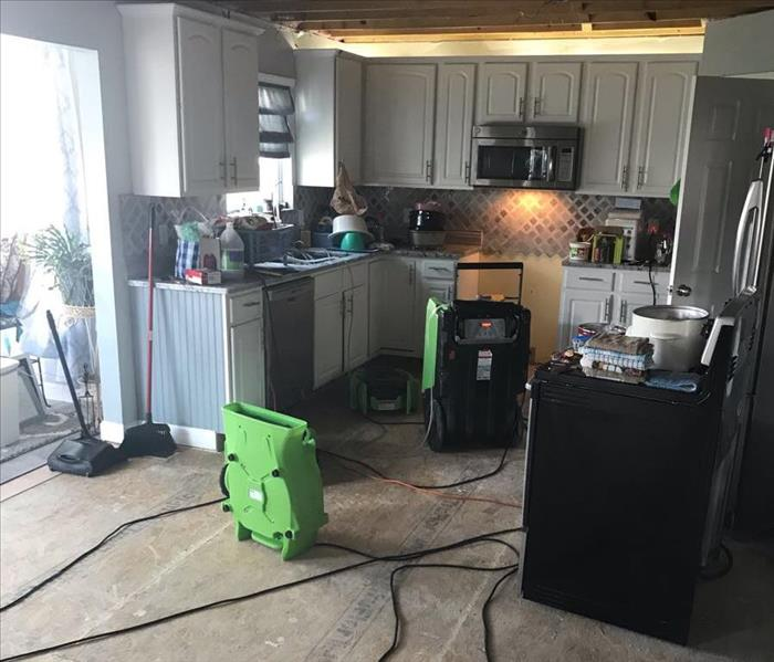 Kitchen with water damage that has dehumidifiers beginning the restoration process.