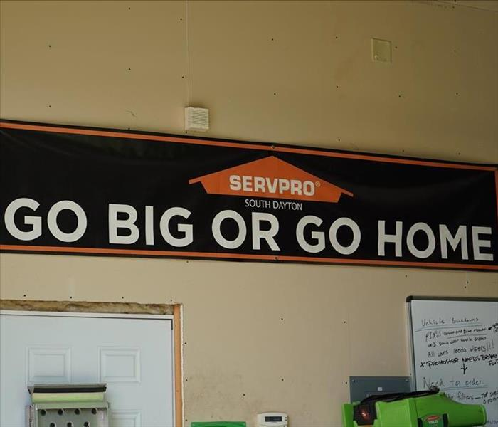 "A SERVPRO banner in the garage that says ""Go Big or Go Home."""