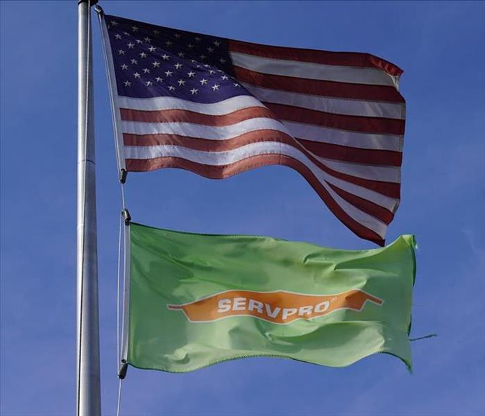 A flag post holds two flags waving in the wind, an American flag and a SERVPRO flag.