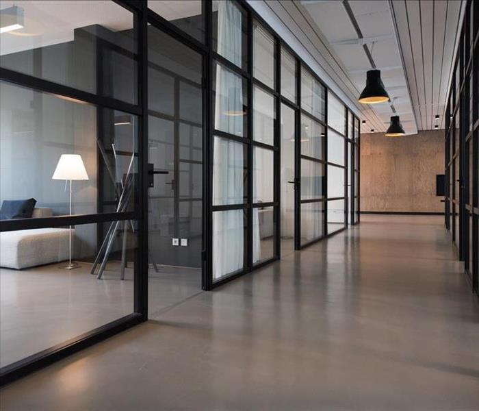 A hallway in an office space, with large windows as the walls. You can see into every office space.