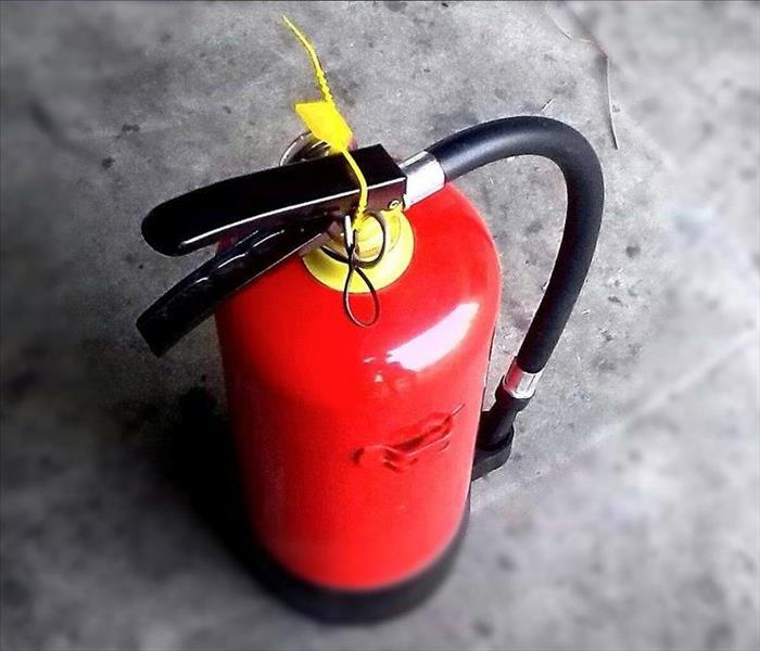 A red fire extinguisher on a concrete floor.