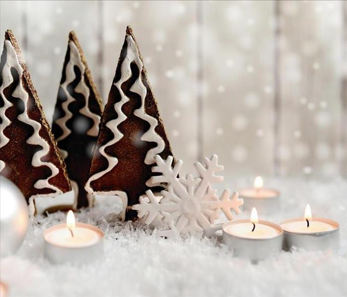 Lit candles beside Christmas tree decorations, on top of fake snow.