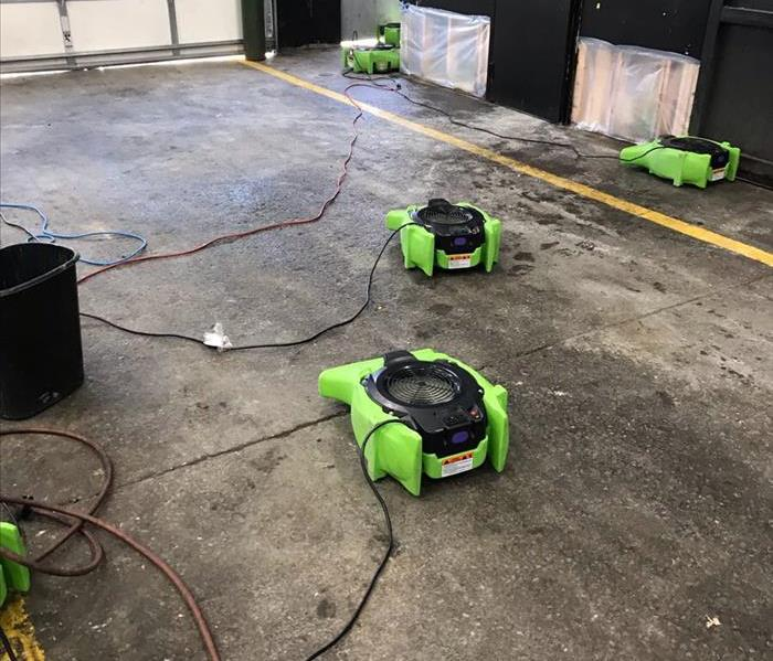Dehumidifiers placed in the empty garage of a Love Tires.