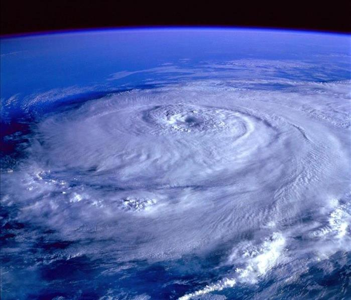 A hurricane formation over the Earth, displaying the eye of the storm at the center.