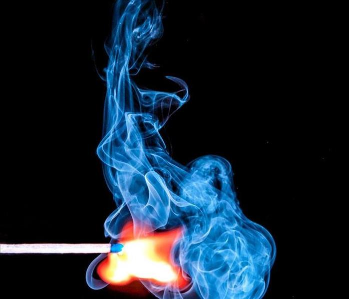 A match ignites a flame that is orange and then turns blue.