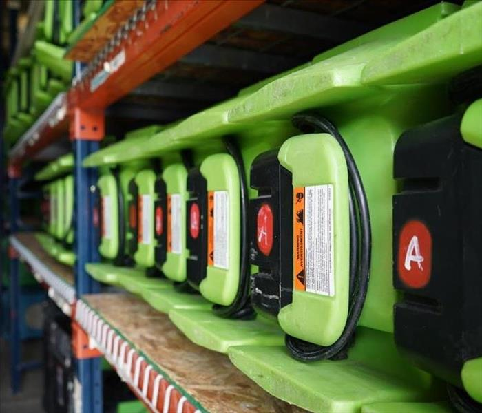 A row of air movers are lined up on a shelf at a SERVPRO garage.