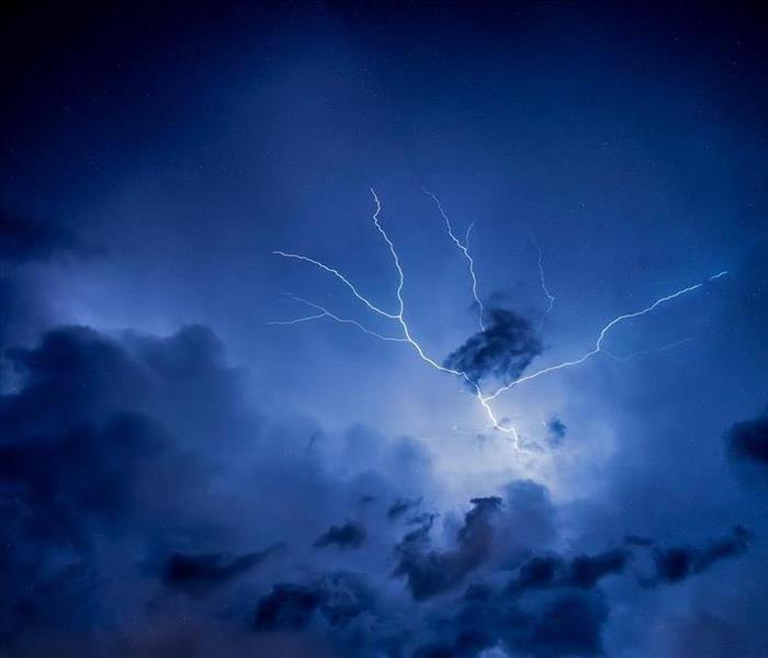 A dark blue, cloudy sky with a white strike of lightning going through the clouds.