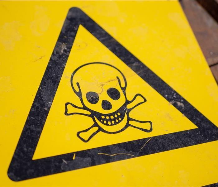 A yellow sign in the shape of a triangle with a skull and cross bones, indicating a dangerous poison.