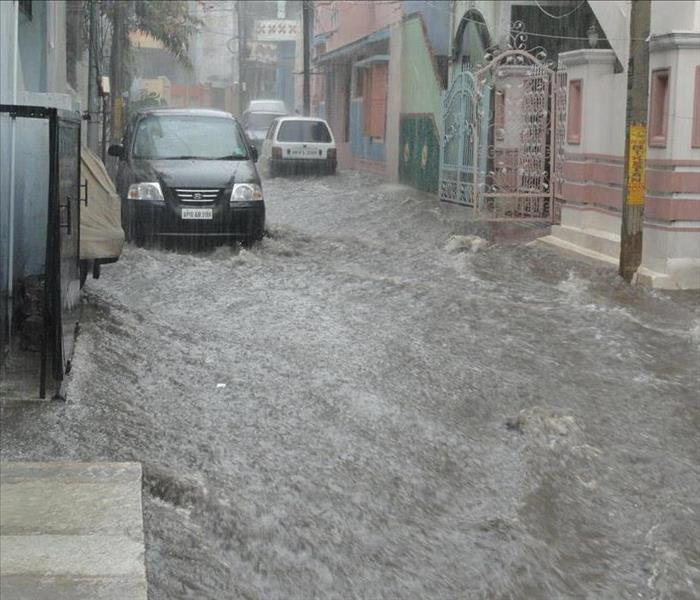 A street is flooded with water, rushing past buildings and cars, covering the entire street.