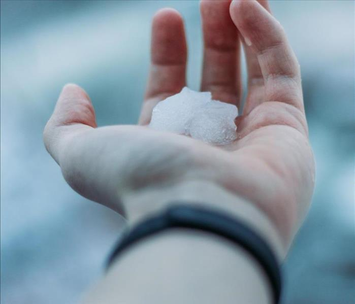 Hand holding one inch sized hail ball in Dayton Ohio