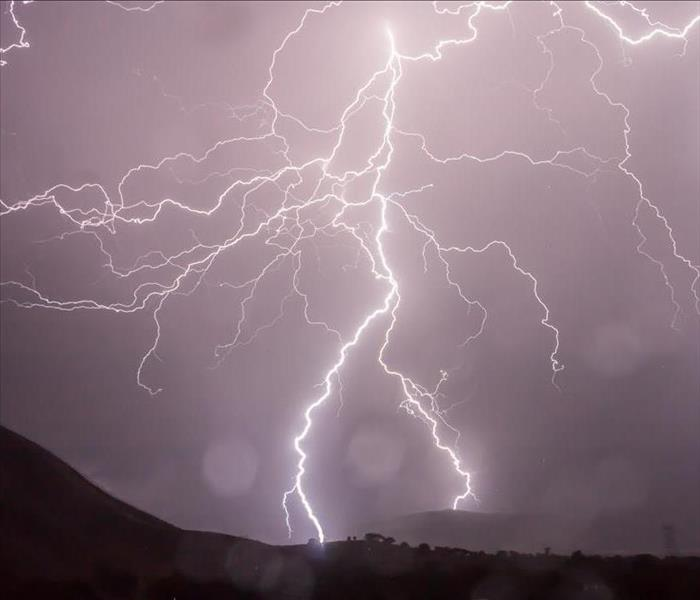 A lightning strike so bright that it lights the entire sky in a pink tone. The strike hits a tree on a black mountain.