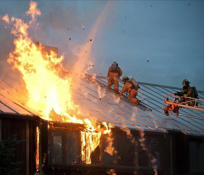 Three firemen are on top of a roof, holding a house in order to spray a fire down.